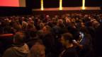 Ein Kinosaal, in dem alle Sitze besetzt sind, aber noch das Licht brennt.