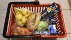 Ein oranger Einkaufskorb, darin Teigwaren, ein Salatkopf, ein Brot und andere Lebensmittel.