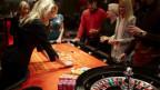 Eine Gruppe von Besuchern spielt Roulette im Casino Zürich.