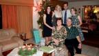 Hans-Georg Bosch Sitz neben seiner Frau im Wohnzimmer. Rundherum stehen seine drei erwachsenen Kinder.