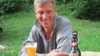 Max Waelti sitzt vor selber gebrautem Bier.