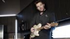 Chris Young mit weisser Gitarre an Tisch angelehnt