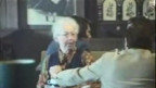 Ausschnitt Versteckte Kamera 1974. Frau lacht nur als der Schauspieler sein Gipfeli in ihren Kaffe tünkelt.