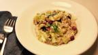 Ein Teller mit weissem Quinoa und Rosenkohl-Blättern und Mandeln.