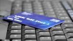 Eine Tastatur, darauf liegt eine unkenntliche Kreditkarte
