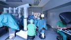 Ein Operationsbett, darüber grosse weisse Roboter-Balken, welche eine Gruppe von Chirurgen bei der Operation unterstützen, im Vordergrund rechts ein Chirurg mit Operationskleid und Kopf- und Atem-Schutzmaske an einem Spezial-Computer mit Blickschutz-Tunnel