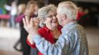 Eine ältere Frau und ein älterer Mann erfreuen sich auf der Tanzfläche.