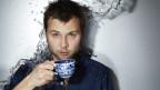 Nils Althaus stehend mit einer Tee- und Untertasse in den Händen