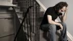 Mann sitz auf Treppe, Kopf in die Hànde gestützt, sehr verzweifelt