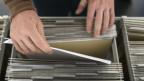 Eine Hängeregistratur von oben, zwei ältere Hände blättern in den Dokumenten