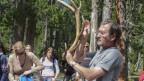 Mann mit Hirschgeweih in der Hand erklärt im Nationalpark den Besuchern, was sie vom Geweih ablesen könnenWald erklärt Besuchern