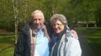 Therese Girod steht mit ihrem Mann im Park. Sie trägt weisses Haar und eine Brille. Um den Hals herum einen blauen Schal.