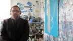 Tristan Rain trägt einen schwarzen Kittel und eine schwarze Brille. Der Vollbärtige sitzt in seinem Atelier. Im Hintergrund Bilder und Pinsel.