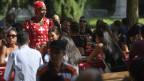 Schwarze Frau in einem roten Kleid voller Schweizer Kreuze.
