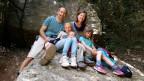 Familie Sarid sitzt auf einem grossen Felsen im Wald.