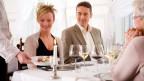 Ein Paar sitzt im Restaurant am Tisch und der Kellner serviert das Essen.