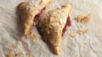 Rechteckige Pies mit Rhabarber-Marzipan-Füllung, mit Mandelblättchen bestreut.