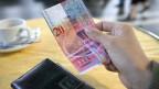 Eine Hand nimmt eine Zwanzigernote aus dem Portemonnaie um einen Kaffee zu bezahlen