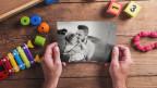 Zwei männliche Hände halten ein Bild von einem Mann mit einem Kind, darum herum liegt Spielzeug