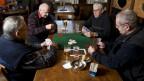 Vier ältere Herren sitzen im Restaurant um einen Tisch und jassen.