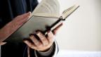 Mann hält Bibel.