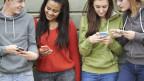 Vier Jugendliche gucken auf ihre Handys.