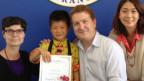 Res Helfer neben einem jungen Schüler. In der hand halten die beiden ein Diplom.