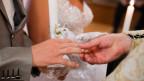 Brautleute stecken sich gegenseitig den Ring über.