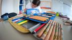 Ein Kind sitzt am Pult, im Vordergrund ein Etui mit Schreibzeug.