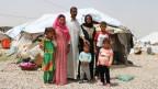Eine Familie steht vor ihrem Zelt in einem Flüchtlinsglager in Nordirak