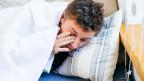 Ein Mann in einem Bett, bis zum Kopf in Decke und Kissen gehüllt, schlaflos, reibt sich mit der rechten Hand das rechte Auge, am rechten Bildrand der Rand eines hellbraunen Regalbodens.