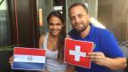 Porträt eines jungen Paares, sie hält eine Flagge aus Paraguay, er eine aus der Schweiz.