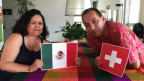 Porträt eines Paares, sie hält die Flagge aus Mexiko, er die Flagge aus der Schweiz.