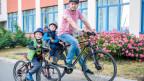 Eine kleine Strasse, darauf steht ein Vater mit seinem Velo, auf dem Kindersitz den Kleinsten, nebeben ihm der Grosse mit dem Kindervelo, alle tragen Helm