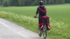 Frau fährt mit Velo am grünen Wegrand vorbei.