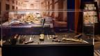 In einer Glasvitrine sind verschiedene Ess-Bestecke zu sehen, dahinter ein gedeckter Tisch