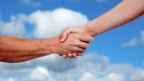Eine männliche Hand schüttelt eine weibliche, dahinter ist eine Wolke zu sehen.