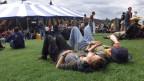 Zwei junge Menschen liegen auf einer Wiese und ruhen sich aus, im Hintergrund Open Air-Betrieb