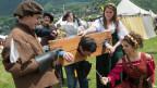Junge Menschen in mittelalterlichen Kleidern stellen eine Szene am Pranger nach