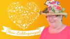 Jeannette Baumgartner mit einem bunten Hut aus lauter Blumen.