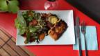 Panierte Risotto-Plätzli und Salat auf einem weissen Teller.