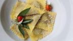 Ravioli, garniert mit Tomaten und Salbei in einem weissen Teller.