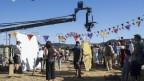 Eine Kamera steht vor einem Zirkuszelt und filmt eine Szene mit Menschen.