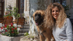 Eine Frau mit ihrem Hund vor einem Landhaus.