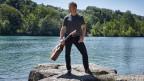 Henä am Fluss mit Gitarre in der Hand