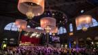 Die festlich beleuchtete Halle des Hauptbahnhofs Zèrich, Blick auf Hunterte von Tanz-Paaren in allen möglichen Kleidungen und eine Bühne mit dem Festorchester.