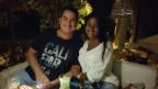 Michael Bonin und Ehefrau Valeria Dias Bonin sitzen auf einem weissen Sofa unter freiem Himmel. Abendstimmung.