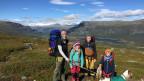 Die Familie in der leicht gewellten Landschaft Lapplands.