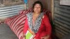 Eine Frau sitzt in einer Hütte in Nepal und hält Hefte in der Hand