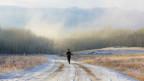 Frau joggt in Winterlandschaft.